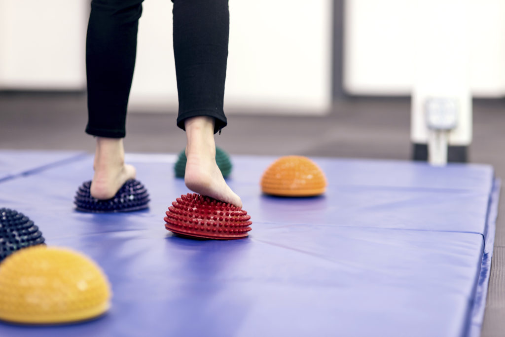 Feet stepping on therapy balls to practice balance at a PT clinic