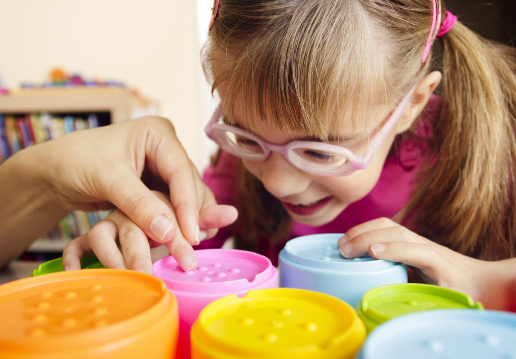 Little girl with poor vision is playing with colorful tactile toy cups as a part of occupational therapy with her teacher.
